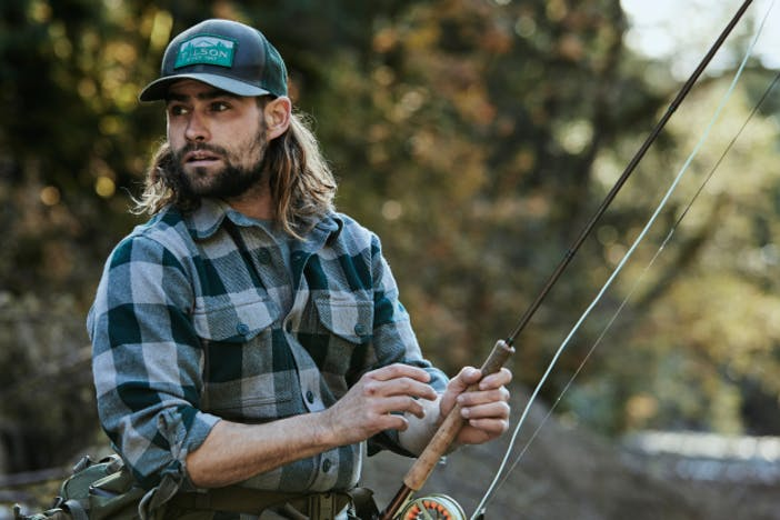 man with long hair in blue and white flannel and green filson hat holding a fly fishing rod