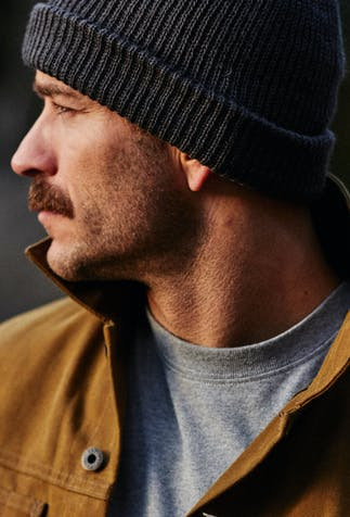 man in thin tan coat wearing a gray beanie