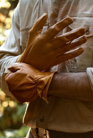 hand pulling a tan leather glove onto his other hand