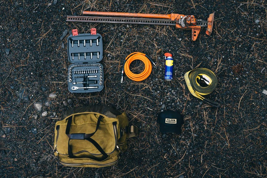 various tools for changing a tire laid out on ground with tan filson duffel and black filson hat