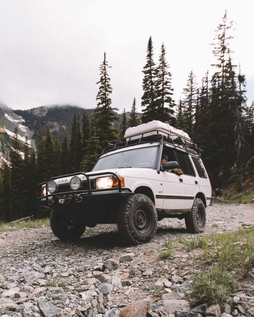 white land rover with gear rack and floodlights on rocky road with pine forest and mountains in background