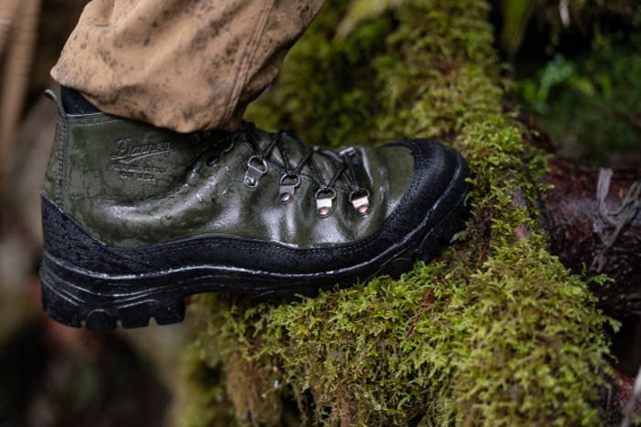 green and black danner x filson boots walking over mossy log