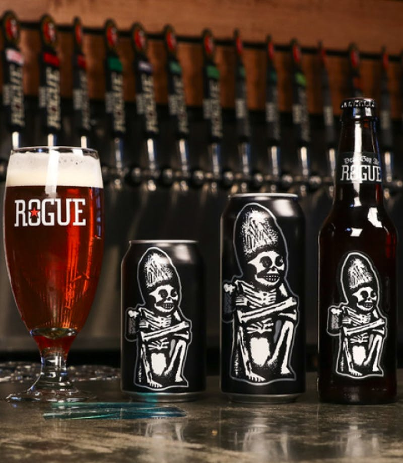 collection of rogue canned and bottled beers of different sizes in front of a line of