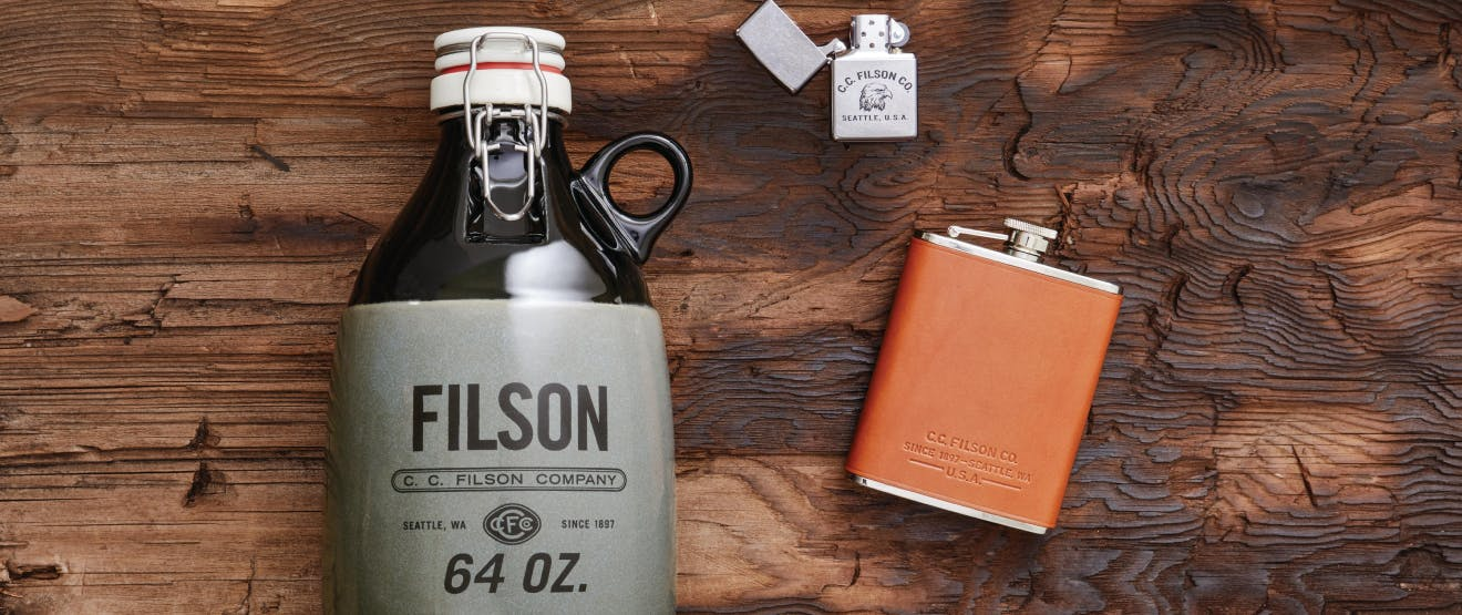 filson 64 oz. bottle, with resealable top, flask with burnt orange leather, and cc filson stainless steel lighter