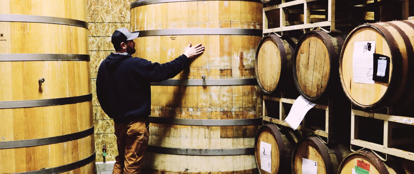 man touching the side of a very large barrel that is three men wide and 8 feet tall at rogue brewery