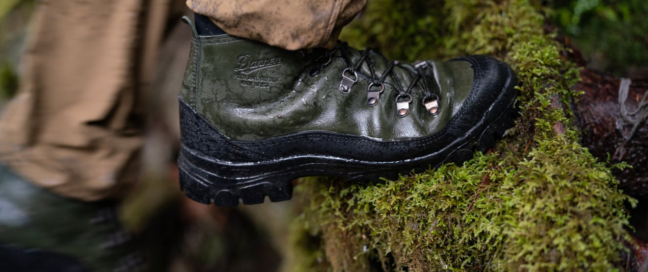 Closeup of green and black waterproof hiking boot by Danner x Filson walking over a mossy log