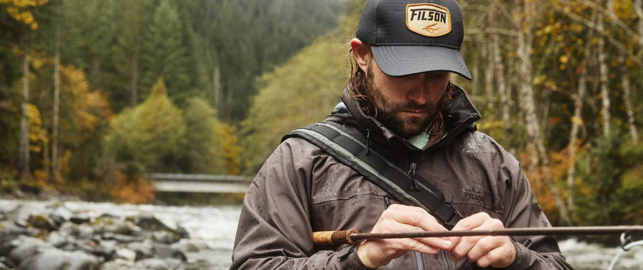man putting line on his fly fishing rod wearing brown filson rain coat and black filson cap standing in river