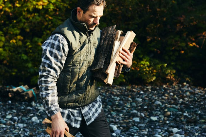 man in green vest and green and white plaid shirt holding an armful of firewood while walking on a rocky beach