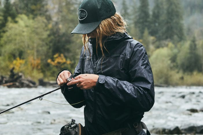 woman in black rain jacket and green filson hat adjusting the line on her flyfishing rod in front of a river