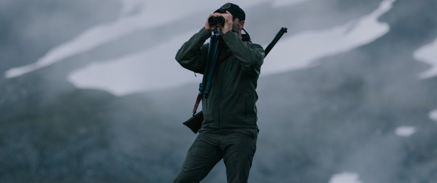 Man with rifle slung over his shoulder standing on rocky outcropping looking through field glasses wearing NeoShell Reliance Jacket