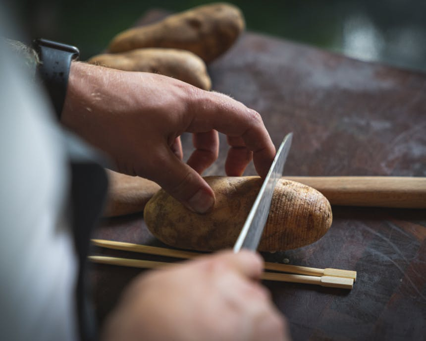 hands holding a knife making cuts for hasselback potatoes with chopsticks and a wooden spoon as a guard