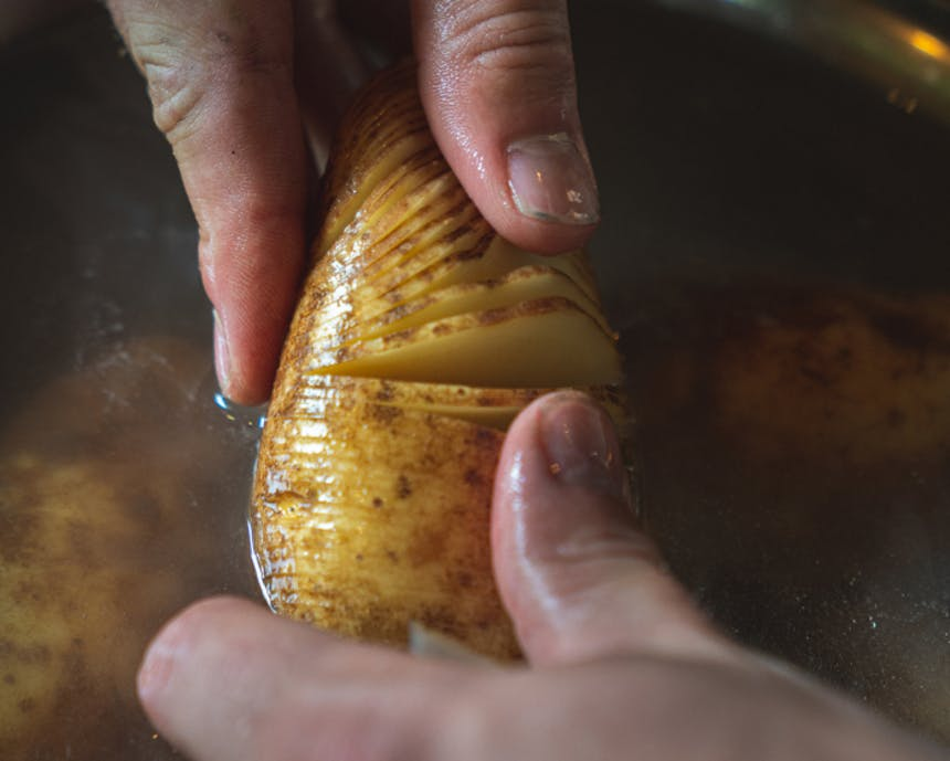 hands spreading apart the fine cuts of a hasselback potato in water