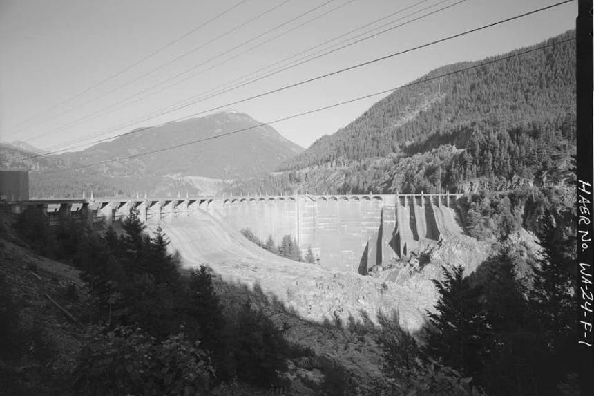 black and white image of dam with pine covered mountains in background