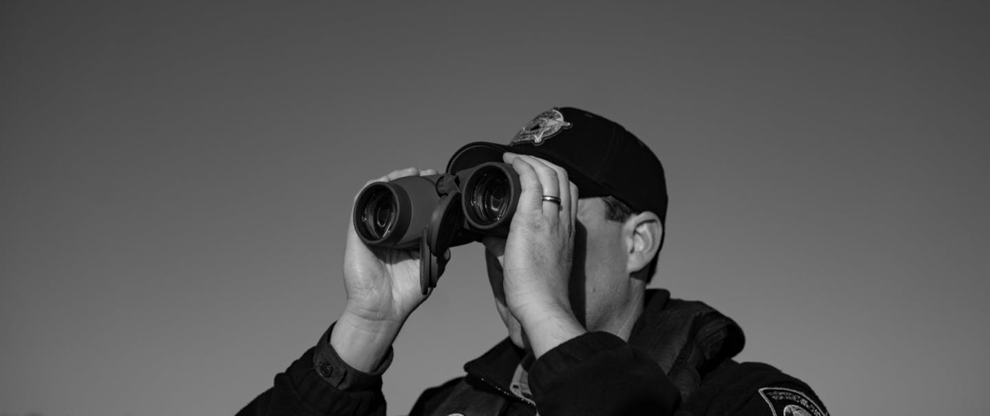 black and white image of fish and wildlife officer looking through binoculars