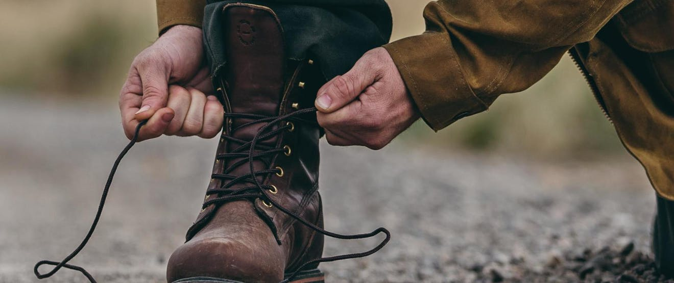 hands tying tall brown boots