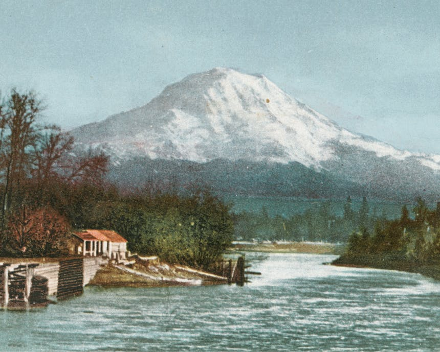 old color photo of a red roofed structure on the side of a river with a snowy mountain in the distance