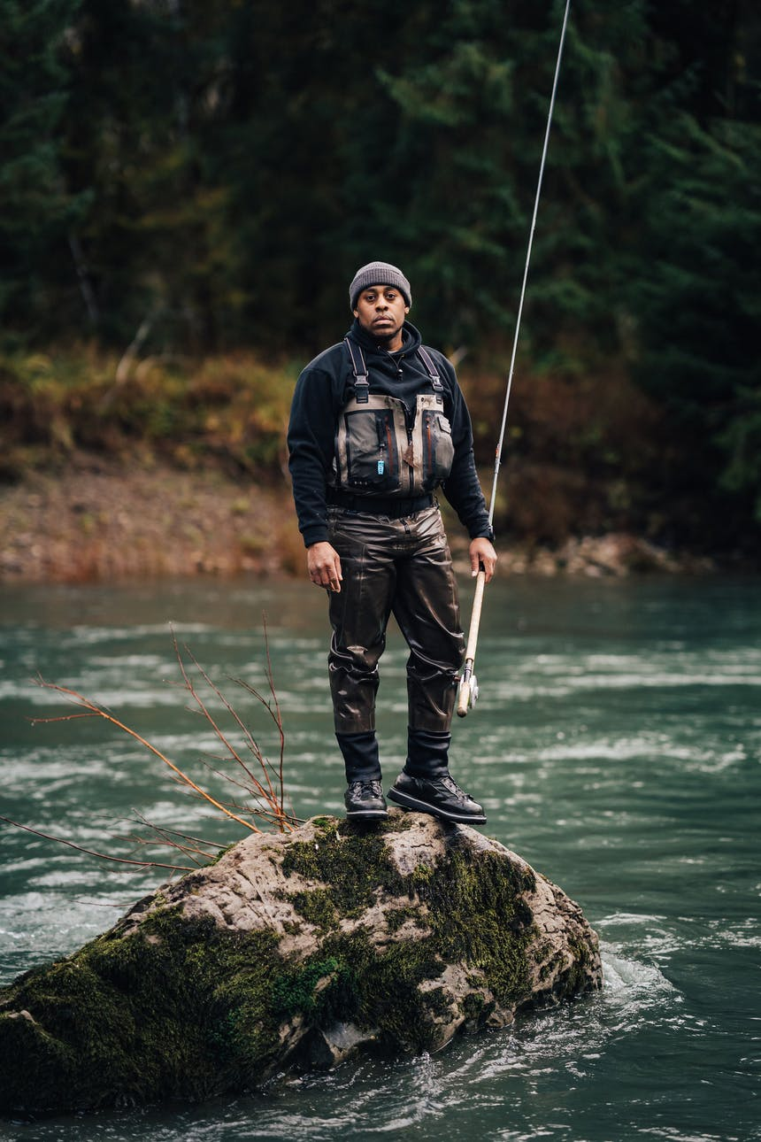 ben matthews wearing dark waders and a fishing vest holding a fly fishing rod standing on top of a rock in the middle of river
