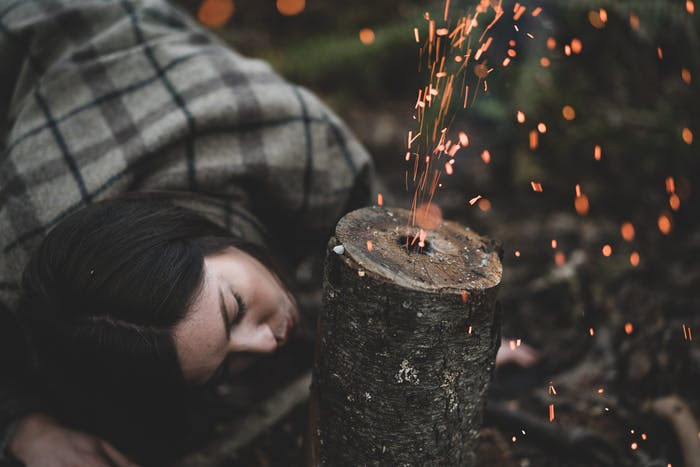 woman in brown and gray flannel shirt blowing through the side of a rocket stove sending sparks out of the central hole in the log