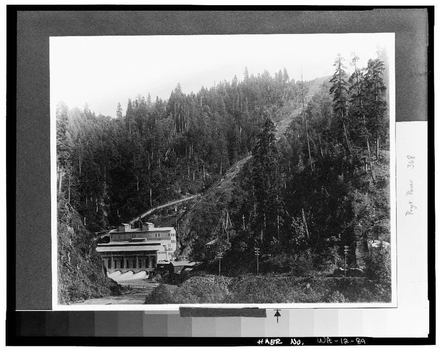 concrete dam building at the mouth of the river with pine trees in the background