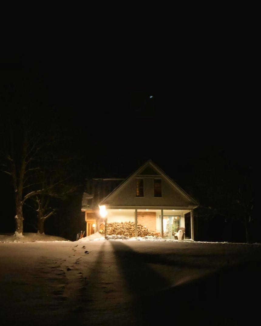 porchlight illuminating a lonely house in a snowy field at night