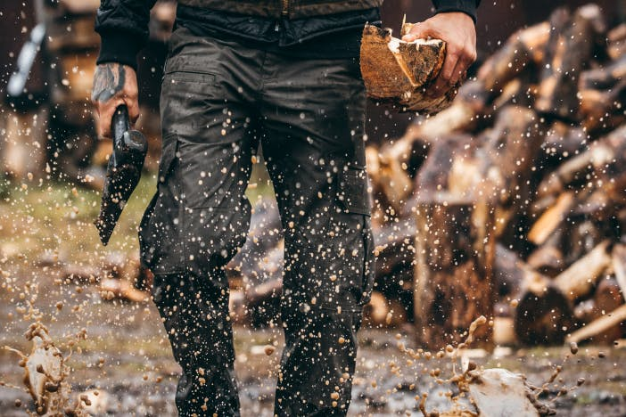 person splashing water while walking in muddy wet pathway holding a log in one hand and an axe in the other