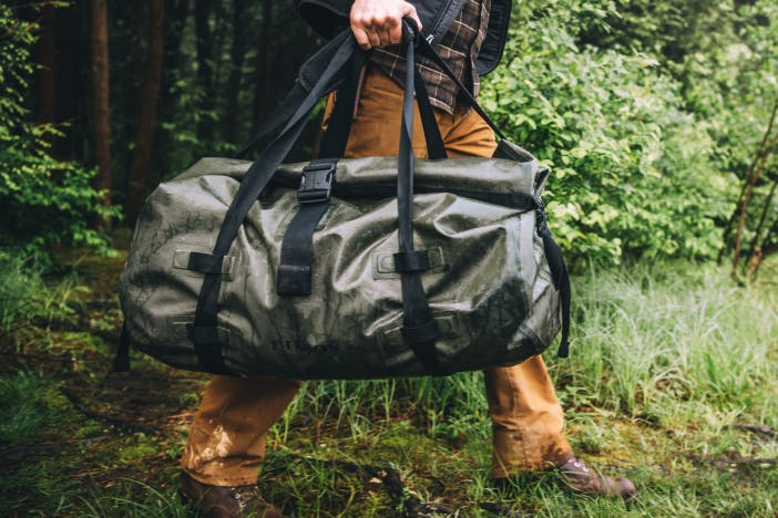person holding an olive colored waterproof filson duffel bag in a forest meadow