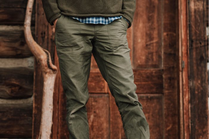 person with hands in pockets of olive green pants standing in front of a well worn wooden door