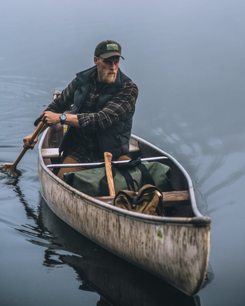 man in vest and brown filson cap paddling a single person canoe with waterproof duffel in boat