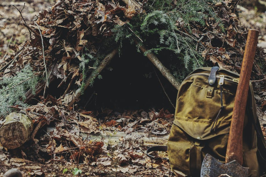 improvised lean to with pine boughs supported by wooden cross braces on leaf covered ground with tomahawk and filson backpack in front of entrance