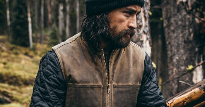 man in waxed cotton vest sitting in forest