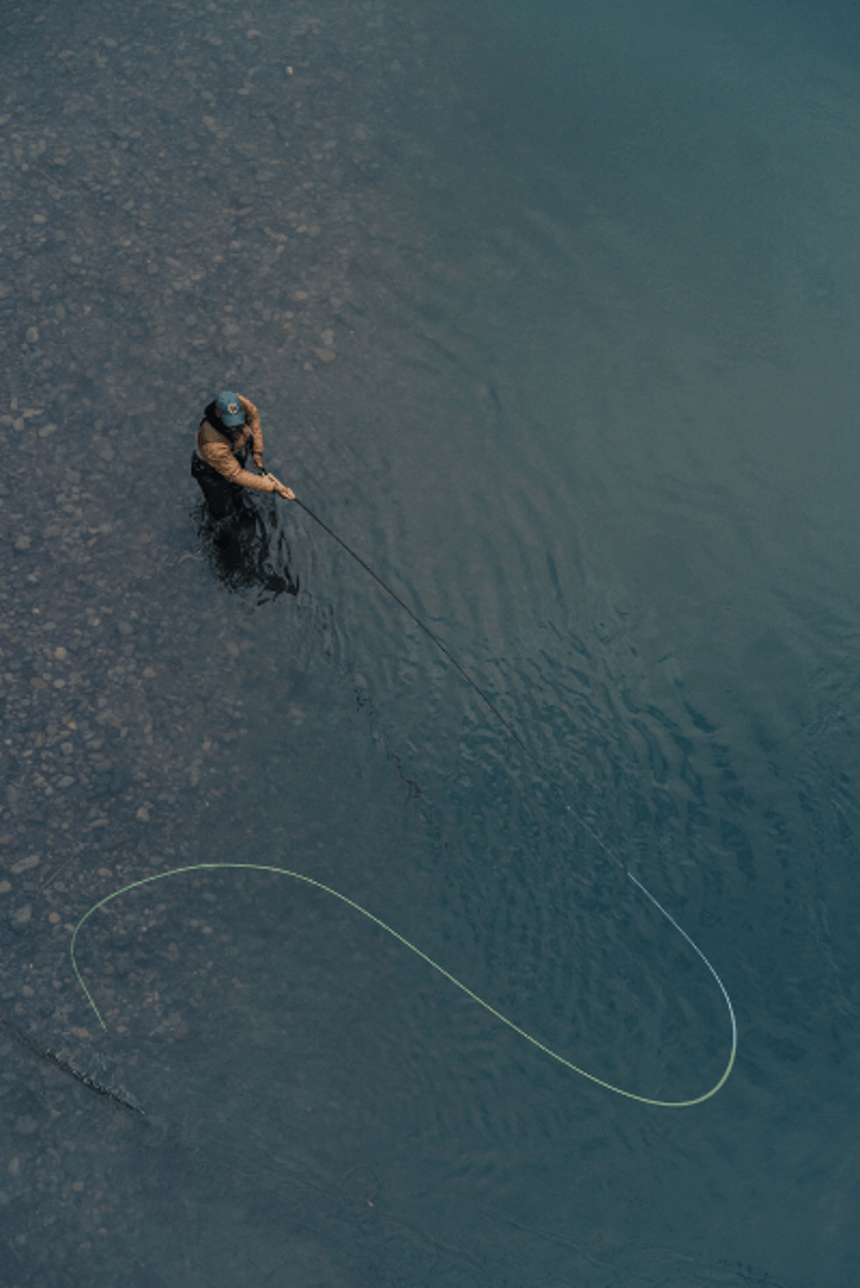 top down view of person casting a fly fishing rod while standing in shallow water