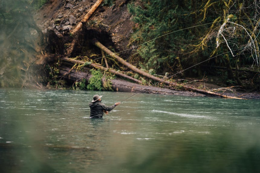 man in chest high water casting a fly fishing rod