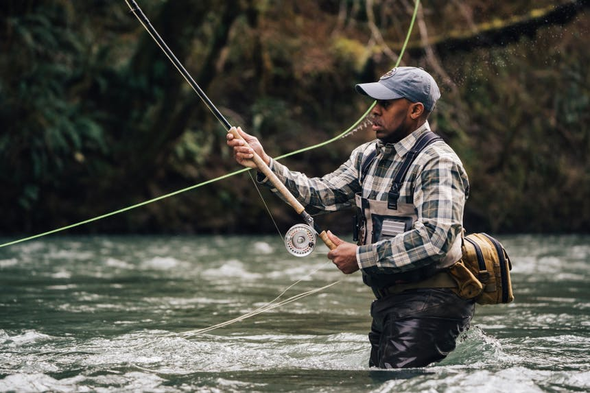 man casting fly fishing rod while wading in river