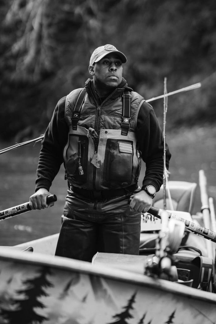 man holding oars while standing in boat