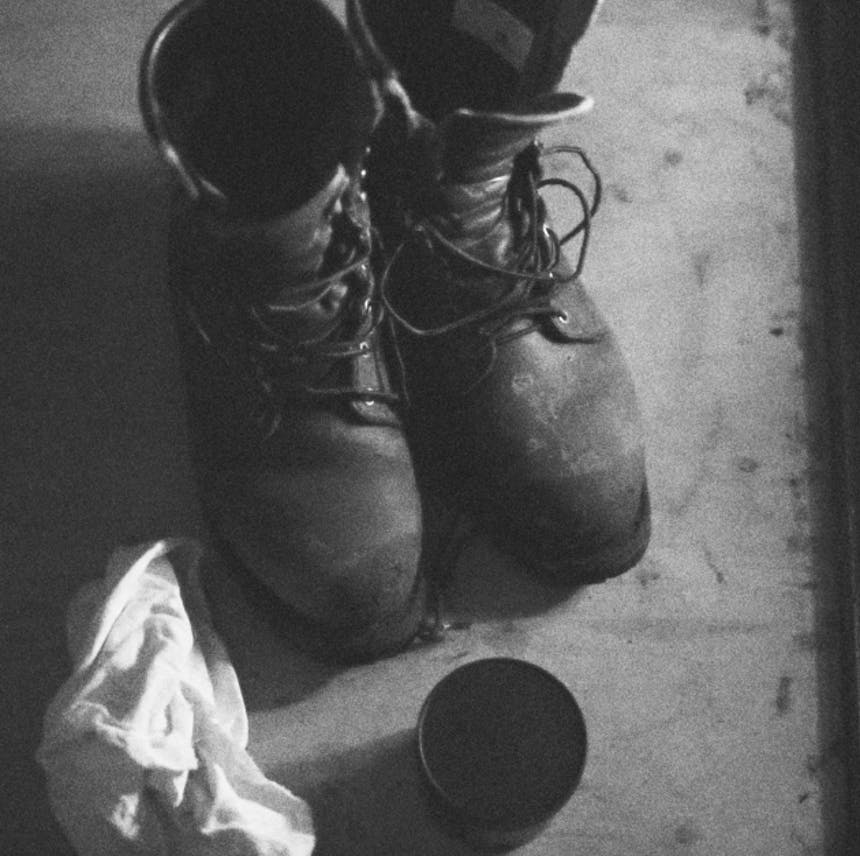 black and white image of workboots with a cloth and polish