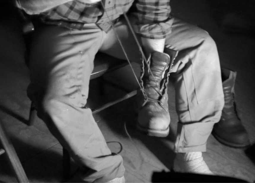 person sitting with hand inside boot, removing shoelaces
