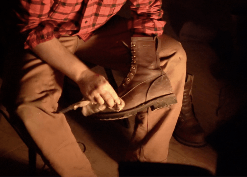 hand holding boot administering polish to brown leather boot