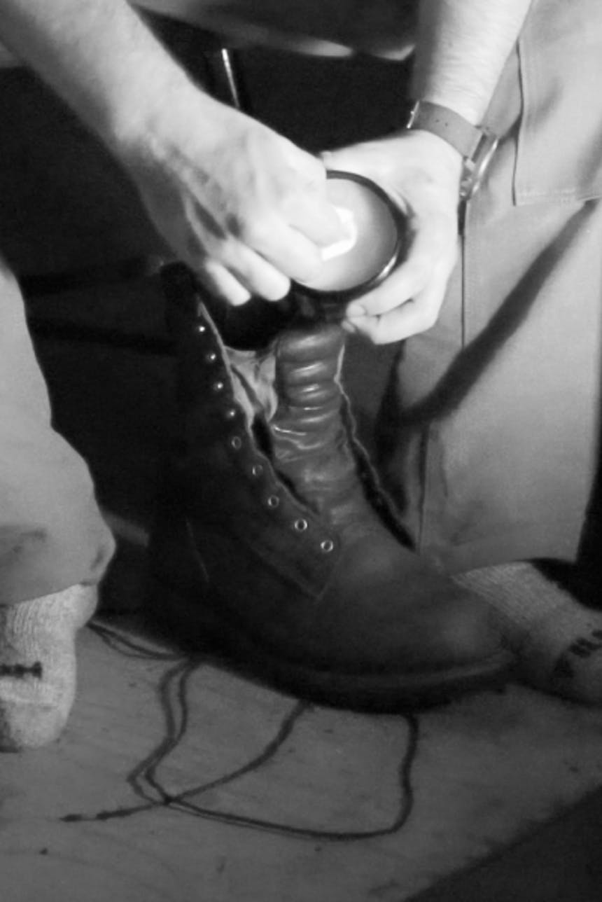 hand holding tin of polish preparing to administer with cloth to unlaced boot