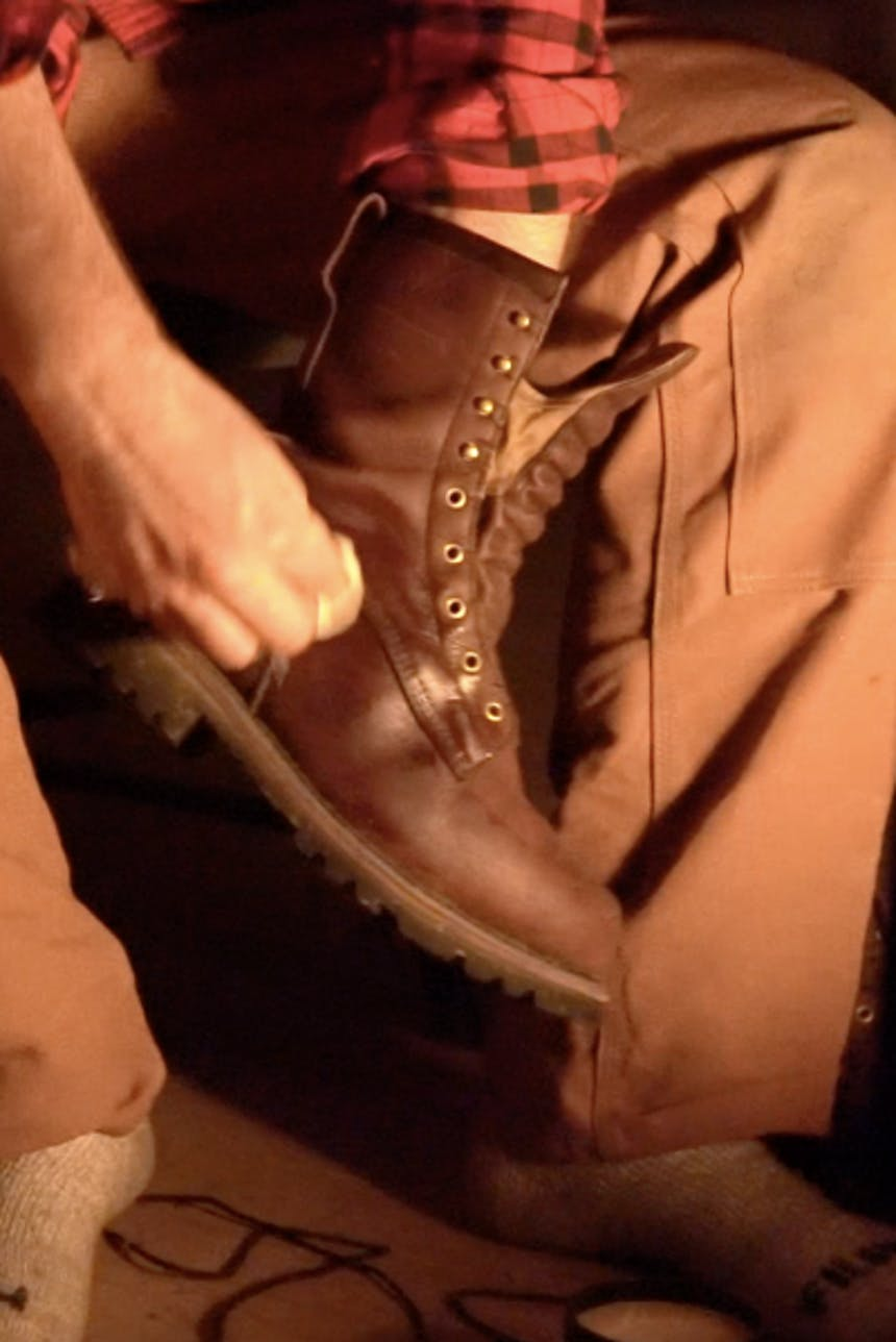 hand administering polish to unlaced brown boot with cloth