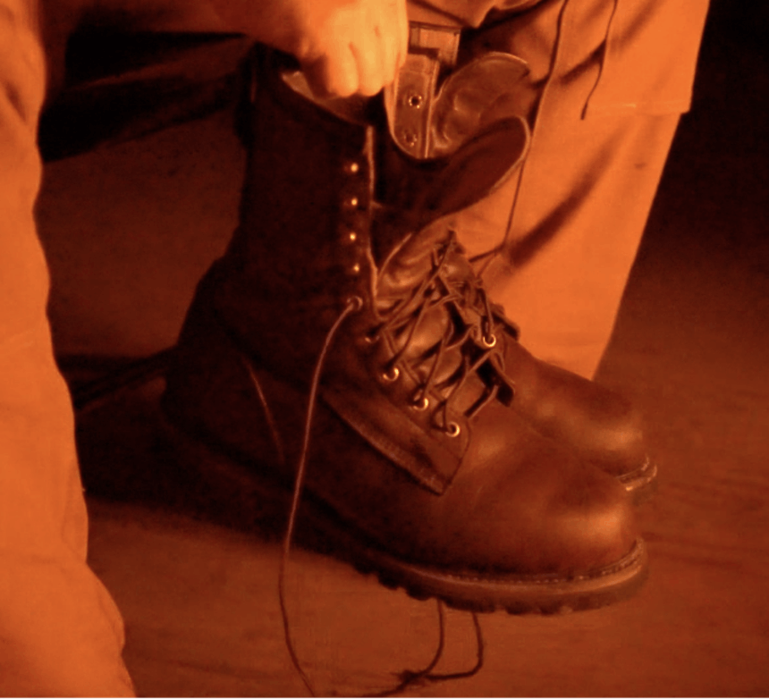 hand holding two pairs of brown boots