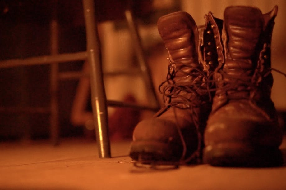 two partially laced boots sitting next to a chair