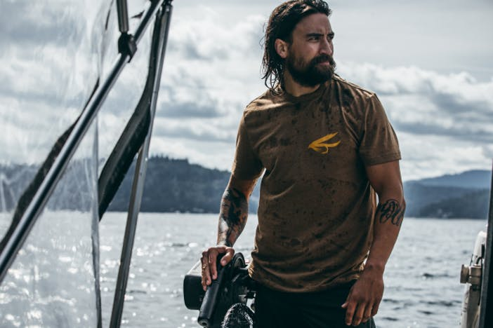 man with black forearm tattoos and a brown shirt standing by the outboard motor of a small boat on the water