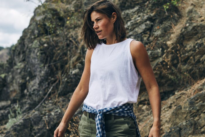 woman with white tanktop and shoulder-length brown hair standing in front of a rocky hillside