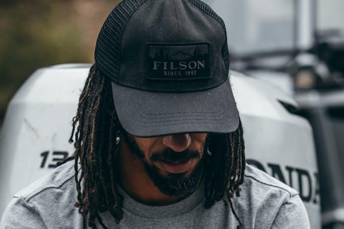 man with thin braids wearing a black filson hat