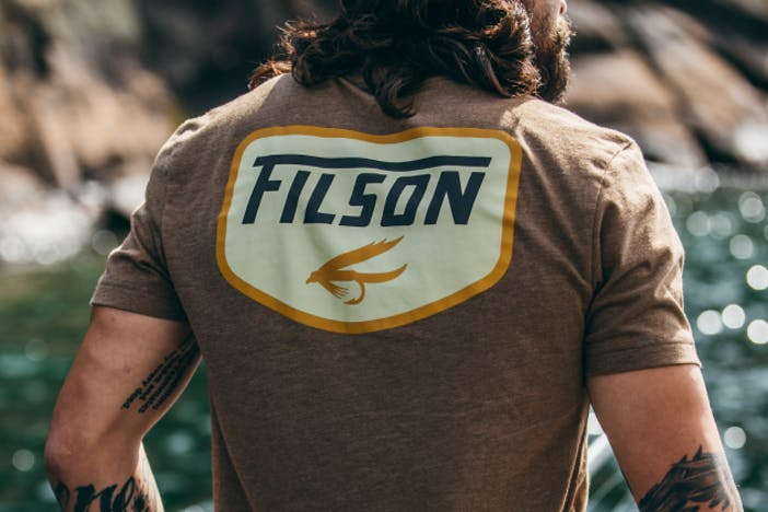 man with black tattoos wearing a brown filson shirt with large blue and white logo