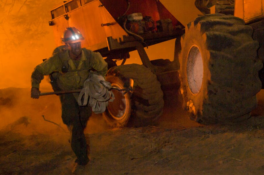 wildland firefighter running holding a bundle of material in front of some large machinery reflecting the orange glow of the fire