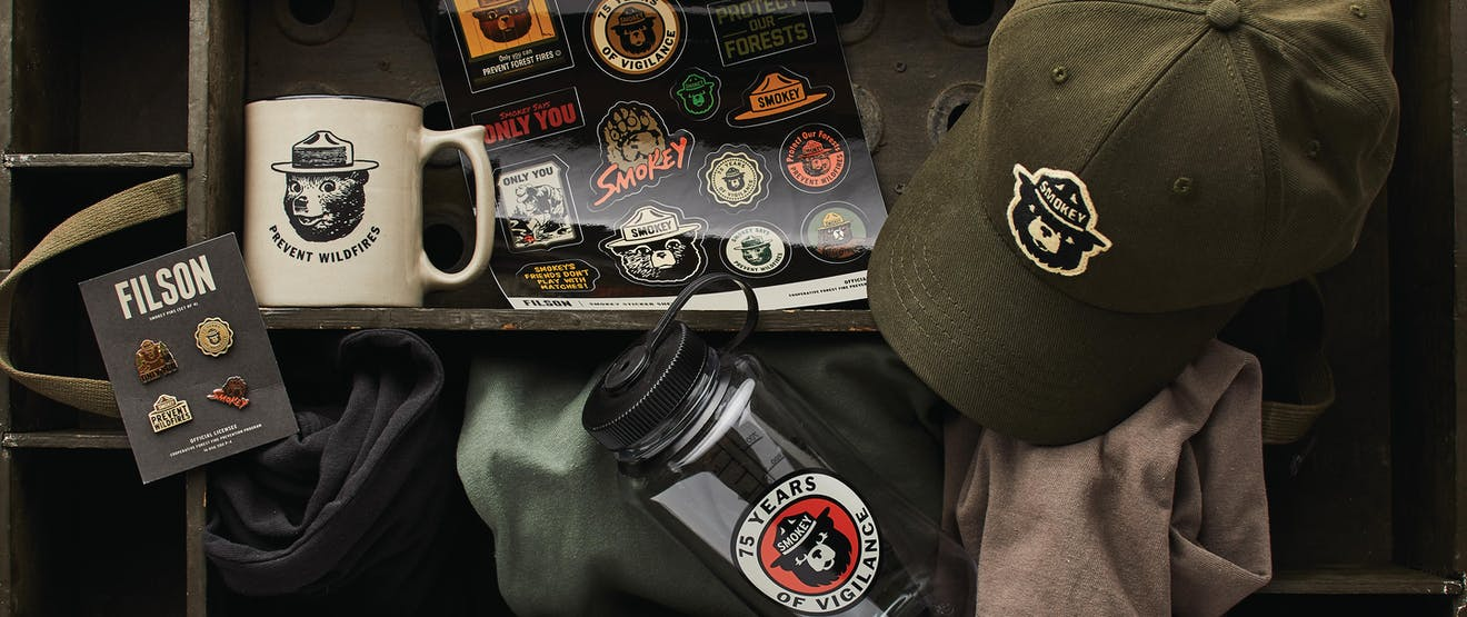 top down view of smokey the bear x filson gear, water bottle, stickers, hat, pins