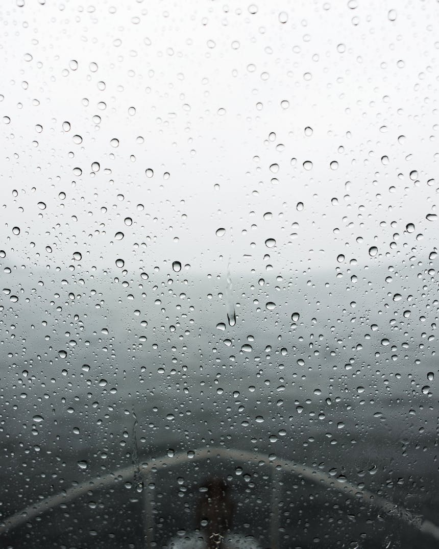 the bow of a ship is seen through a rain covered pane of glass