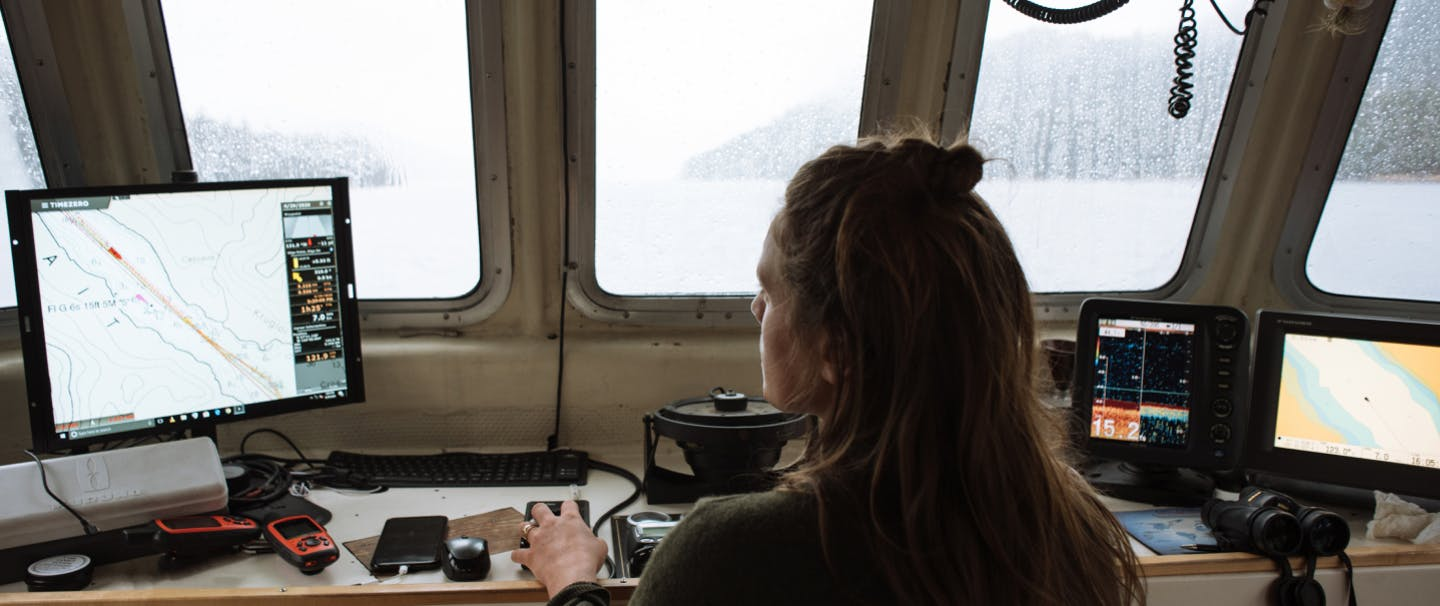 woman using a computerized navigation system on the bridge of a fishing vessel
