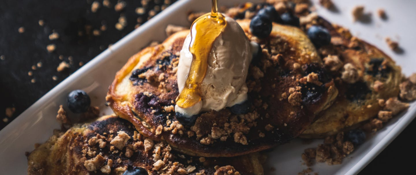 syrup drizzling over a quenelle of butter on top of a trio of blueberry pancakes on a white plate